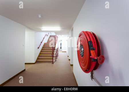 Fire hose on wall inside building by staircase. - Stock Image