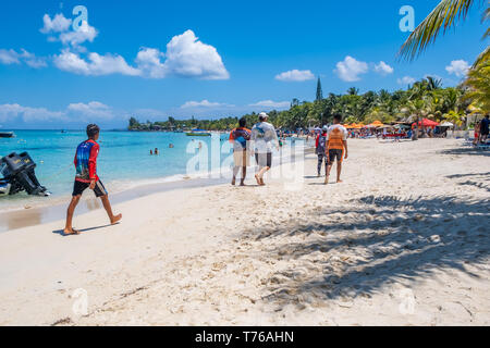 Tourists and locals stroll along West Bay Roatan Honduras on a beautiful sunny day. - Stock Image