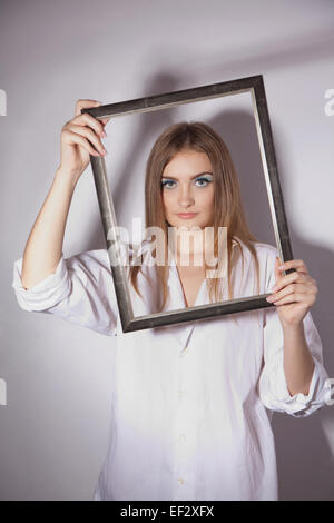 Sad beautiful girl holding a frame in his hands - Stock Image