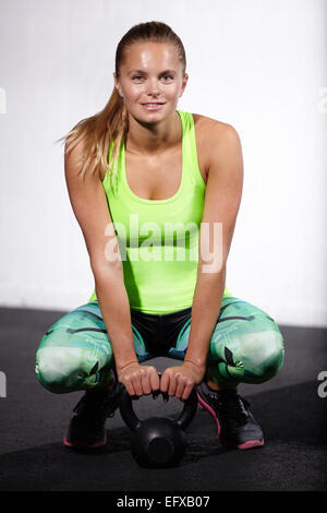 Portrait of young woman crouching with kettle bell in gym - Stock Image