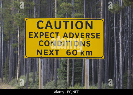 Caution sign on Spray Lakes Road warns about possible adverse conditions on back country roads in Alberta near Banff and Canmore. - Stock Image