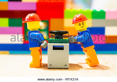 Poznan, Poland - March 14, 2019: Two Lego construction workers pushing together a safe. - Stock Image