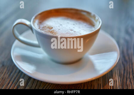 Hot Cappuccino In White Cup On Wooden Table placed centrally - Stock Image