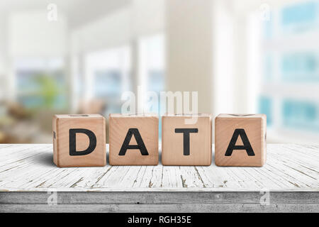 Data sign on a table with white planks in a bright room in daylight - Stock Image