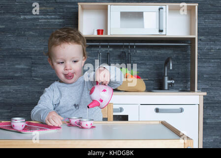 Little girl playing with toy tea set - Stock Image