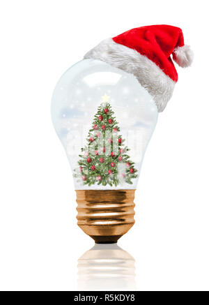 Snow globe light bulb wearing Santa hat with decorated Christmas tree and copy space. Glowing Xmas season and bright New Year. - Stock Image