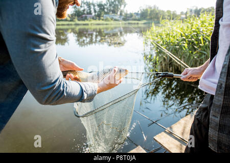 Fisherman getting caught fish from the fishing net near the lake in the morning - Stock Image