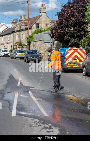 A wessex water engineer using a listening device to precisely locate an underground burst pipe that is leaking into the road - Stock Image