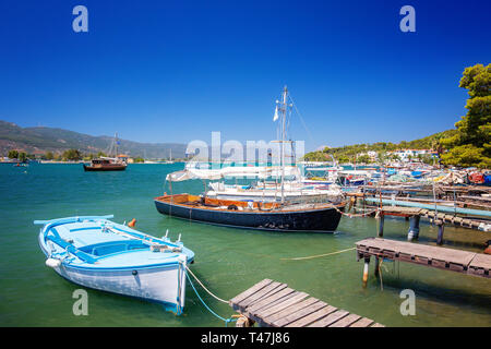 Poros island in a summer day in Greece. Wooden pier with fishing boats at Poros island in Greece - Stock Image