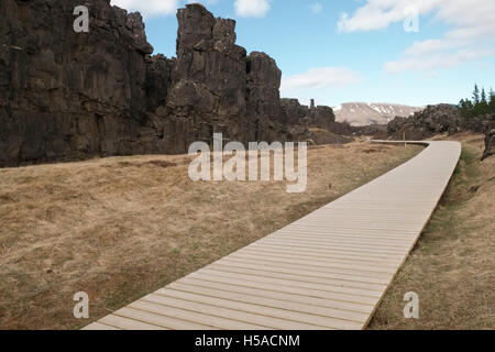 Wooden walkway towards high mountain - Stock Image