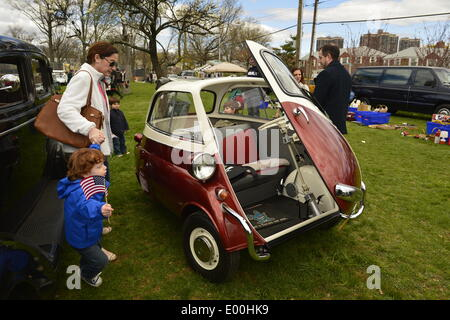 Floral Park, New York, U.S. 27th April, 2014. A family with young children look at the 1958 BMW Isetta 300 at the 35th Annual Antique Auto Show at Queens Farm. Designed by the Italian refrigerator company ISO, it has a refrigerator-like front door which swings open to let the driver and passenger enter. Credit:  Ann E Parry/Alamy Live News - Stock Image