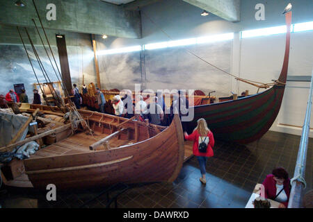 Visitors take a look at reconstructed Viking ships from the 11th century, discoverd in the Roskilde fjord in 1962, - Stock Image