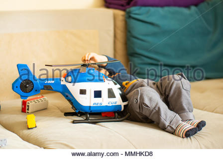 Toy plastic rescue helicopter next to a baby boy on a couch - Stock Image