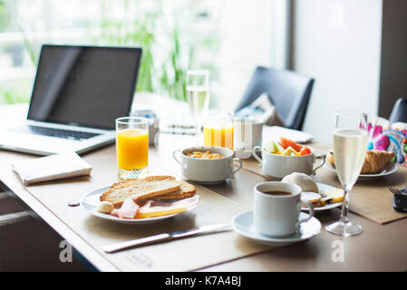 Breakfast on table beside laptop computer - Stock Image