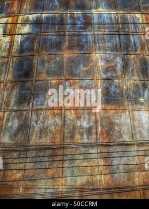 Grungy, rusting metal wall with electric power lines in foreground. - Stock Image