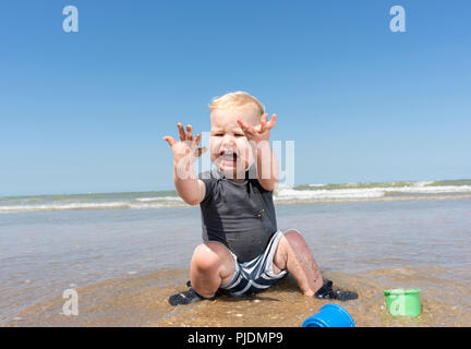 Toddler horrified with sea water on hands on beach - Stock Image