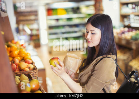 Young woman shopping, examining apple in grocery store - Stock Image