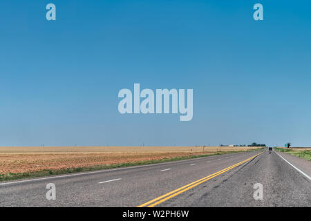Brownfield, USA Texas countryside rural town historic farm road view from 380 highway with prairie dry grass field and blue sky - Stock Image