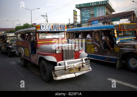 Jeepneys creep along in heavy traffic in Manila, Philippines. - Stock Image