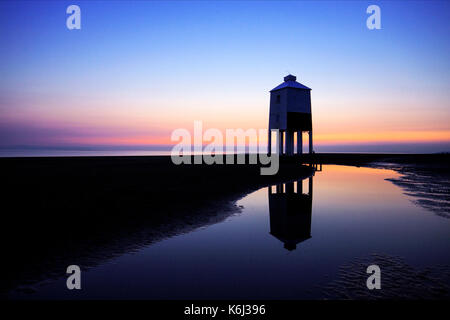 The Burnham on Sea, UK low lighthouse at dusk just after sunset. Reflected in a large pool of seawater on the beach. - Stock Image