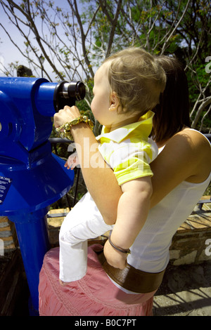 Mother and toddler looking through a telescope Mijas Pueblo, Costa del Sol, Andalusia, Spain - Stock Image