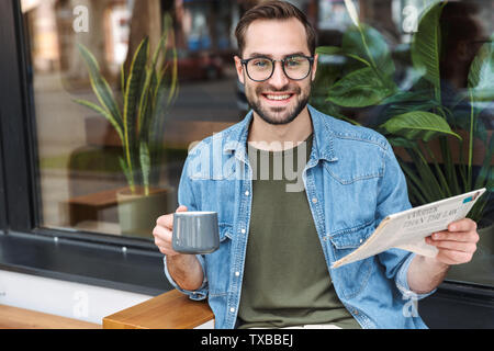 Photo of european happy man wearing denim shirt and glasses reading newspaper with cup of coffee in cafe outdoors - Stock Image