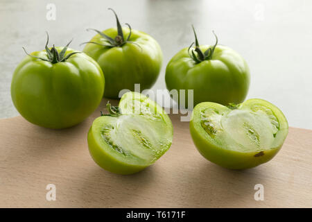 Whole and half fresh raw green unripe tomatoes on a cutteing board - Stock Image