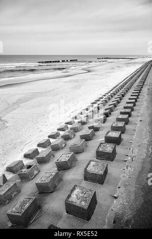 Black and white picture of concrete breakwater on a beach. - Stock Image