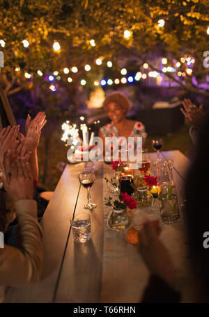 Friends celebrating birthday at garden party table - Stock Image