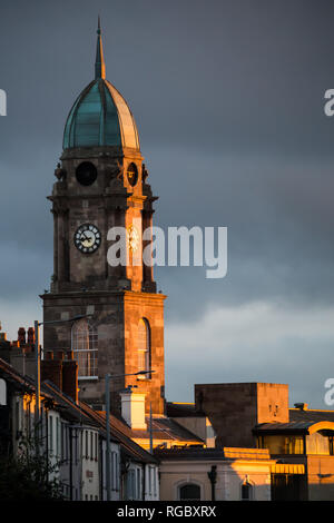 Late evening sunlight shines on the clock tower of the Irish Linen Centre in the centre of Lisburn, N.Ireland. - Stock Image