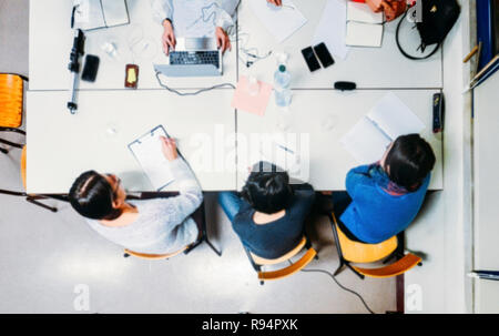 All female corporate office meeting from above with general deliberate blur applied throughout. - Stock Image
