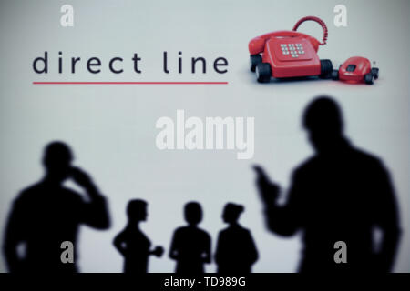 The Direct Line Insurance logo is seen on an LED screen in the background while a silhouetted person uses a smartphone (Editorial use only) - Stock Image