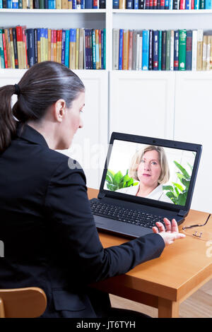 Rear view of a business woman in her office in front of her laptop, having a video call with her physician, telemedicine or telehealth concept - Stock Image