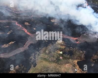 Channelized lava streams down fissure 22 in the East Rift Zone from the eruption of the Kilauea volcano May 23, 2018 in Pahoa, Hawaii. - Stock Image