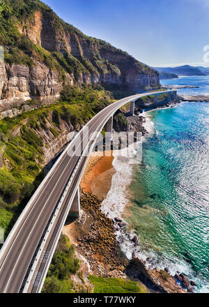 Modern highway of Sea CLiff Bridge around steep sandstone cliffs on Australian pacific coast - part of the Grand Pacific drive. Vertical aerial panora - Stock Image