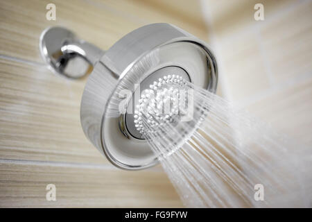 Shower head spraying water in a luxury hotel bathroom - Stock Image