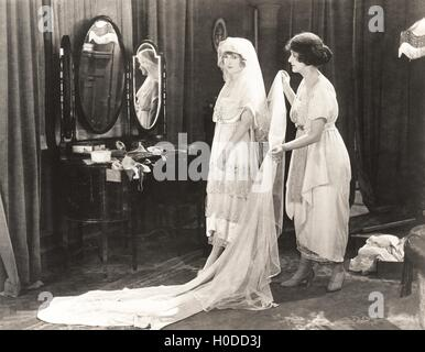 Woman helping bride get dressed - Stock Image