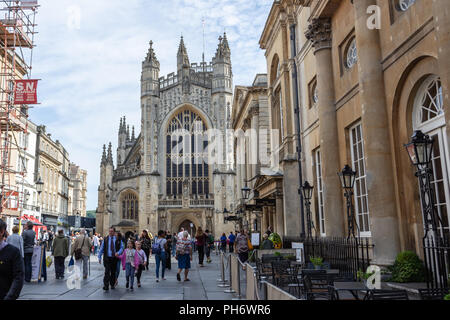 Crowds of people and tourists in the Abbey Churchyard in front of Bath Abbey with the Pump room to the right - Stock Image