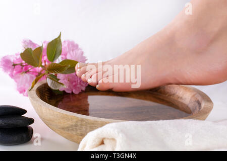 Female feet on wooden bowl with water and pink flower in spa studio. Girl feet with french nails polish. Pedicure and spa concept. Close up - Stock Image
