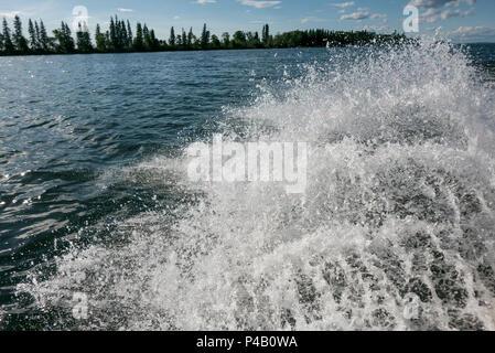 Sun sparkles on fishing boat wake, Dore Lake, Saskatchewan, Canada - Stock Image