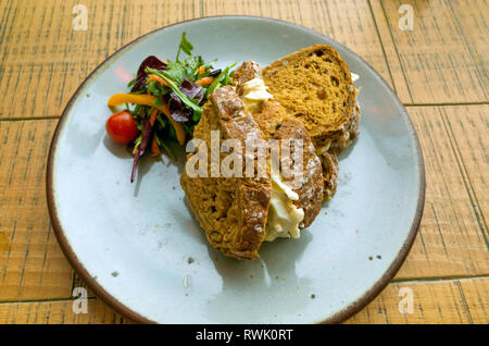 Lunchtime snack Egg Mayonnaise sandwich on brown bread with salad garnish - Stock Image
