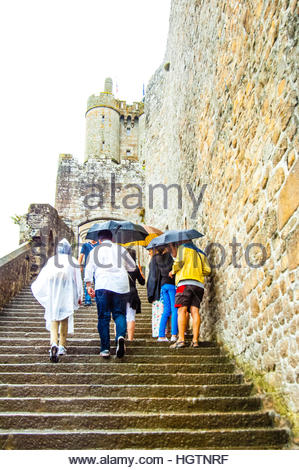 The Island of Mont St Michel on a cloudy & wet day in Normandy, France.People walking with raincoats and umbrellas - Stock Image