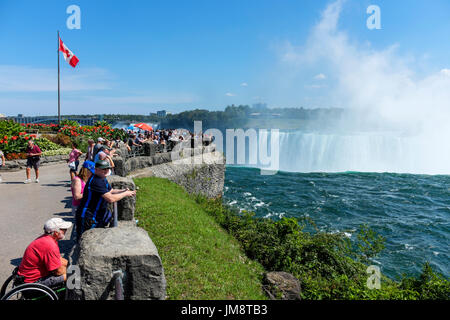 Visitors to Niagara Falls watch the Canadian Horseshoe Falls from a viewpoint. Spray from the Falls is in the air on a sunny day. Canadian flag. - Stock Image