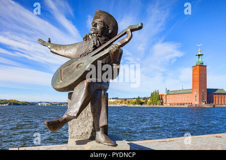 16 September 2018: Stockholm, Sweden - Sculpture of Swedish musician Evert Taube on the Stockholm waterfront. Behind is the City Hall, site of the Nob - Stock Image