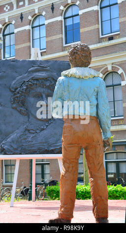 Statue of Rembrandt van Rijn working on a painting at the place he was born (house no longer there)  in the city of Leiden, South Holland, Netherlands - Stock Image
