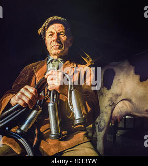 Brecon Beacons,Wales, Uk, November 2,1988: An elderly farmer poses with his milking machine with cows about to be milked in early morning sun. - Stock Image