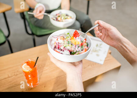 Couple eating salad indoors, cllose-up view from above - Stock Image