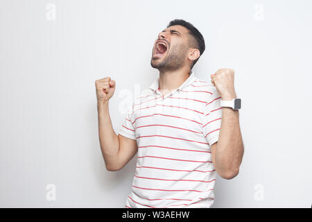 Yes I win. Portrait of happy screaming handsome bearded young man in striped t-shirt standing with fists and rejoicing or celebrating his victory. ind - Stock Image