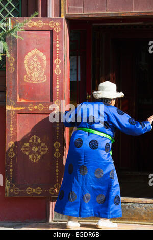 Old Mongolian woman entering a temple, Gandan Monastery, Ulaanbaatar, Mongolia - Stock Image