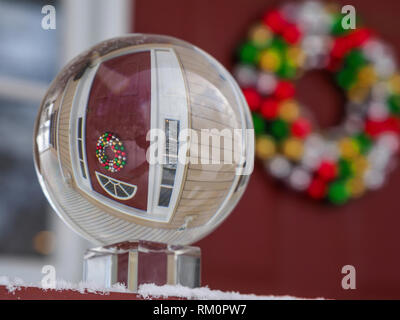 A festive front door seen through a real snow globe at a wintry home. - Stock Image